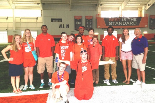 Kaye Stanzione (fourth from right) enjoys a tour of Clemson's indoor football practice facility with ClemsonLIFE students and Clemson staff.