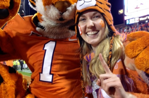 Clemson student Leah Watts poses during a football game with The Tiger mascot.