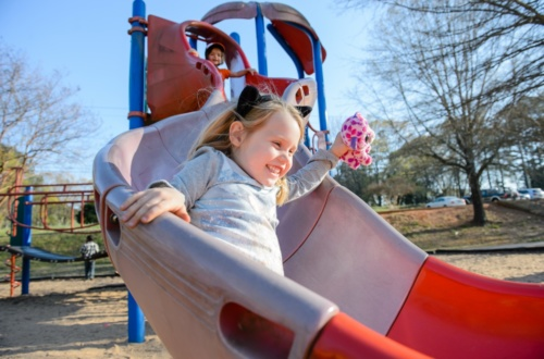 Two children play on a slide on the playground.