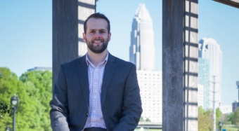 A 2011 business management grad, Brendon Mullen is focused on growing his photo booth business. Here he is pictured with a city skyline in the background.