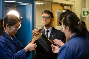 Amod Ogale inspects some carbon fiber with his team in their Earle Hall lab.