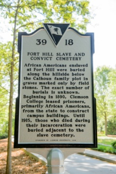 Image of one side of the Clemson historical marker that sits outside the Woodland Cemetery. It reads: Fort Hill Slave and Convict Cemetery. African Americans enslaved at Fort Hill were buried along the hillside below the Calhoun family plot in graves marked only by field stones. The exact number of burials is unknown. Beginning in 1890, Clemson College leased prisoners, primarily African Americans, from the state to construct campus buildings. Until 1915, those who died during their incarceration were buried adjacent to the slave cemetery.