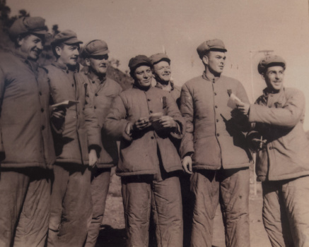 U.S. Army 1st Lt. William H. Funchess (second from right) and some of his fellow prisoners of war stand in new winter uniforms given to them by their Chinese captors in the fall of 1951. (Photo by Frank Noel)