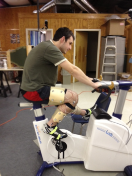 Man on a stationary bike with sensors on his leg peddles in an ACL study.