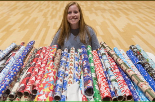 Price Crenshaw smiles behind a table full of wrapping paper rolls.