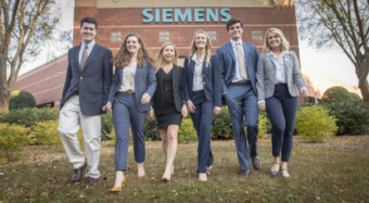 "Six college students dressed in formal clothing walk towards the camera over the grass in front of a building with a big ""Siemens"" sign on the top."
