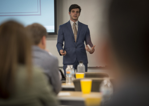 A Clemson student in a suit speaks and gestures, seen between the heads of audience members.