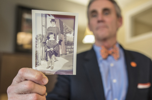 George Petersen holds out a black and white photo of him and his mother, both dressed in graduation gowns and caps, in his office.