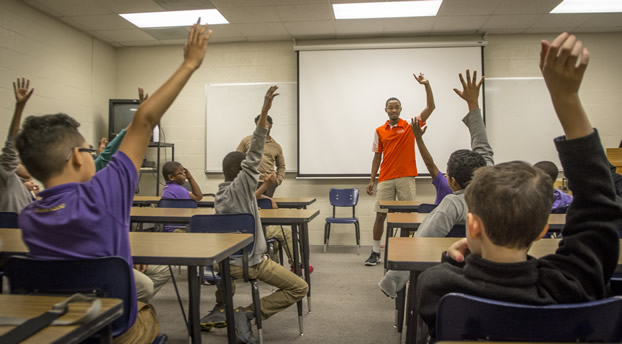 A Clemson student in an orange shirt is surrounded by upraised hands in a classroom.