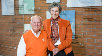 Rob and Claudia Hubbard sit and smile together in a classroom building.