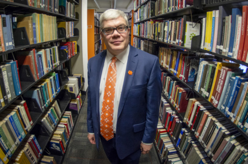 Dean Cox, in a dark blue suit with orange tie, stands between two bookshelves full of books.