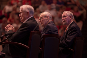 Profile shot of three men in suits with audience in the background