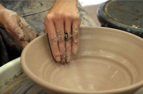 A student shapes a bowl in the studio.