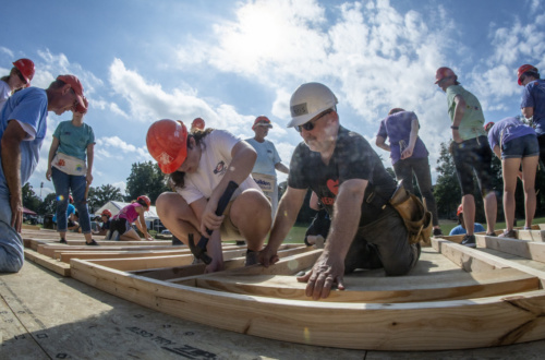 Pastor Chris Heavner holds boards together while a student hammers the board while working on the Habitat for Humanity home build on Bowman Field.