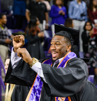 A graduate celebrates before receiving his degree.