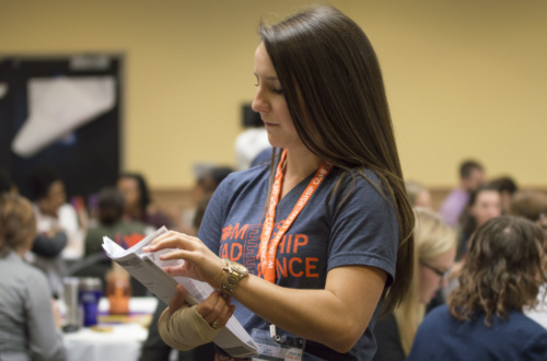 A representative passes out packets at the 2018 Women's Leadership Conference in Hendrix Student Center.