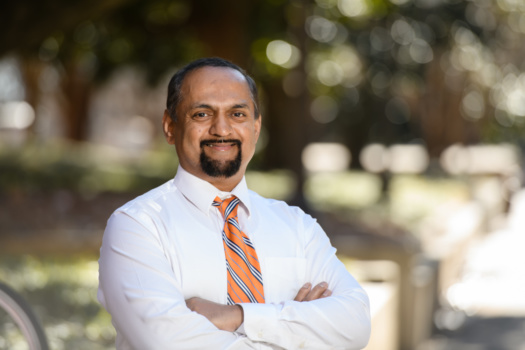 A portrait of Dr. Naren Vyavahare taken outside. Dr. Vyavahare is wearing a white dress shirt and an orange-striped tie.