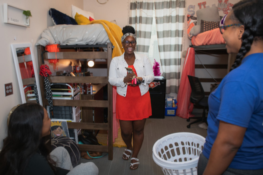 Three women stand in a dorm room laughing.