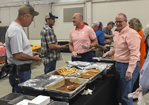 President Clements laughs with several men in plaid shirts and hats, while standing in front of trays of food