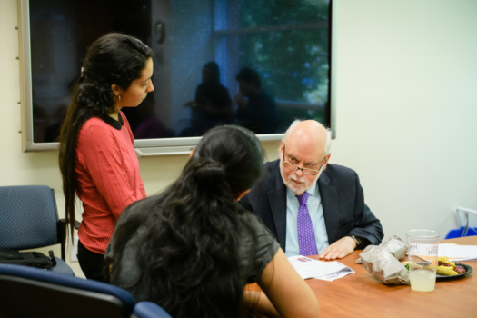Sir Fraser Stoddart talks with two women graduate students in a conference room.