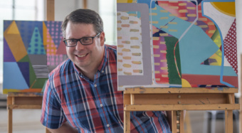 A man wearing a plaid shirt stands next to three easels holding colorful abstract paintings